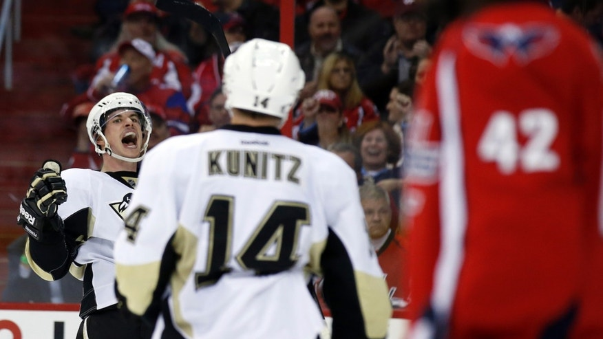 Pittsburgh Penguins center Sidney Crosby (87) celebrates his goal with left wing Chris Kunitz (14) in the second period of an NHL hockey game against the Washington Capitals, Wednesday, Nov. 20, 2013, in Washington. (AP Photo/Alex Brandon)