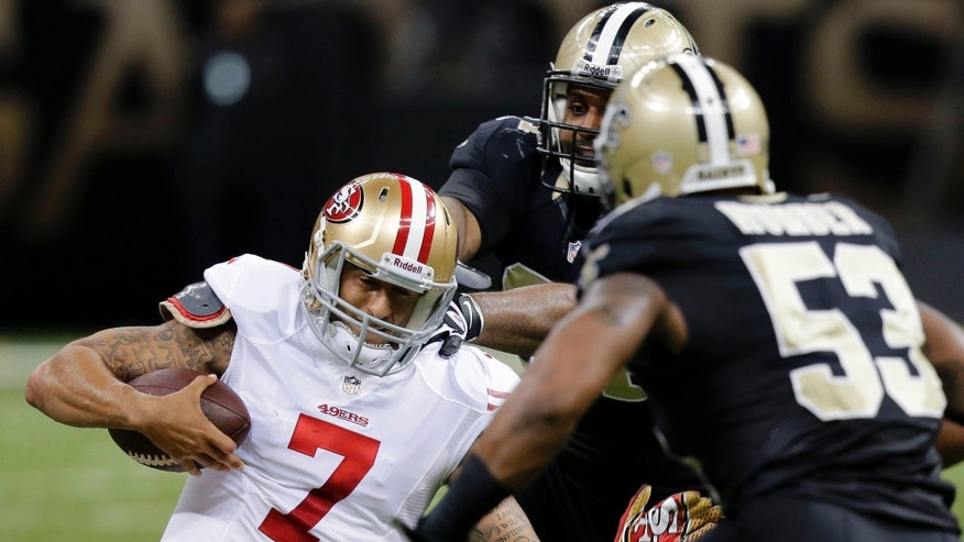 San Francisco 49ers quarterback Colin Kaepernick (7) slides as he is covered by New Orleans Saints defensive end Cameron Jordan and outside linebacker Ramon Humber (53) in the first half of an NFL football game in New Orleans, Sunday, Nov. 17, 2013. (AP Photo/Bill Haber)