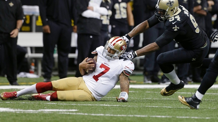 San Francisco 49ers quarterback Colin Kaepernick (7) slides as he is stopped by New Orleans Saints defensive end Cameron Jordan (94) in the first half of an NFL football game in New Orleans, Sunday, Nov. 17, 2013. (AP Photo/Dave Martin)