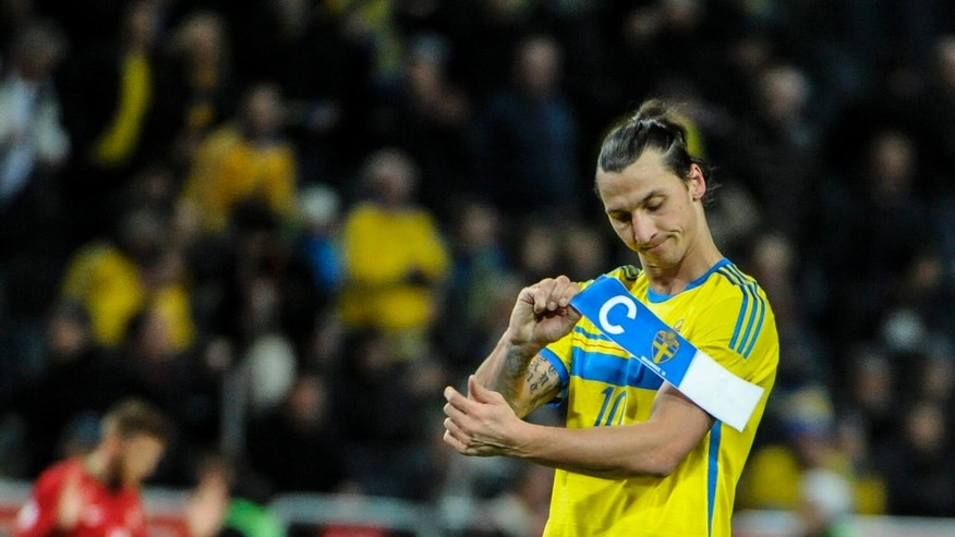FILE - In this Nov. 19, 2013 file photo Sweden's forward Zlatan Ibrahimovic removes the captain's armband, after the World Cup 2014 qualifying playoff second leg soccer match between Sweden and Portugal, at Friends Arena in Stockholm. Sweden lost 2-3. The tournament in Brazil will be a poorer spectacle without Zlatan Ibrahimovic strutting his stuff for Sweden, or Welshman Gareth Bale leaving defenders in his wake with his searing pace. Prolific scorer Robert Lewandowski of Poland, Czech goalkeeper Peter Cech and rising Danish star Christan Eriksen will also be missing from the showcase tournament. (AP/TT/Erik Martensson)  SWEDEN OUT
