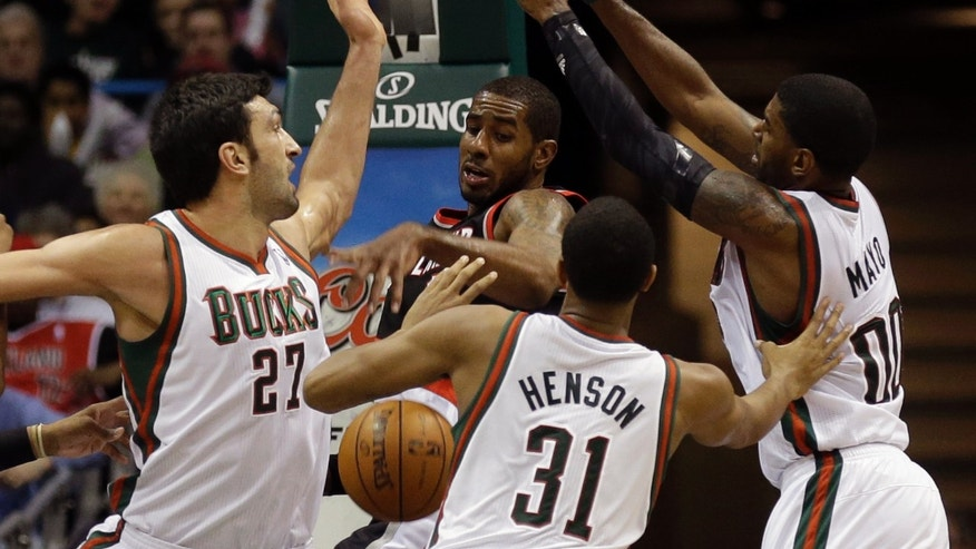 Portland Trail Blazers LaMarcus Aldridge, center, looses the ball against Milwaukee Bucks' Zaza Pachulia (27), John Henson (31) and O.J. Mayo (00) during the second half of an NBA basketball game Wednesday, Nov. 20, 2013, in Milwaukee. (AP Photo/Jeffrey Phelps)