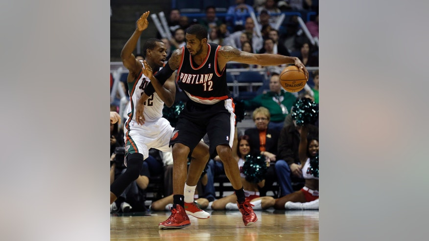 Portland Trail Blazers' LaMarcus Aldridge(12) drives against Milwaukee Bucks' Khris Middleton, left, during the second half of an NBA basketball game Wednesday, Nov. 20, 2013, in Milwaukee. (AP Photo/Jeffrey Phelps)