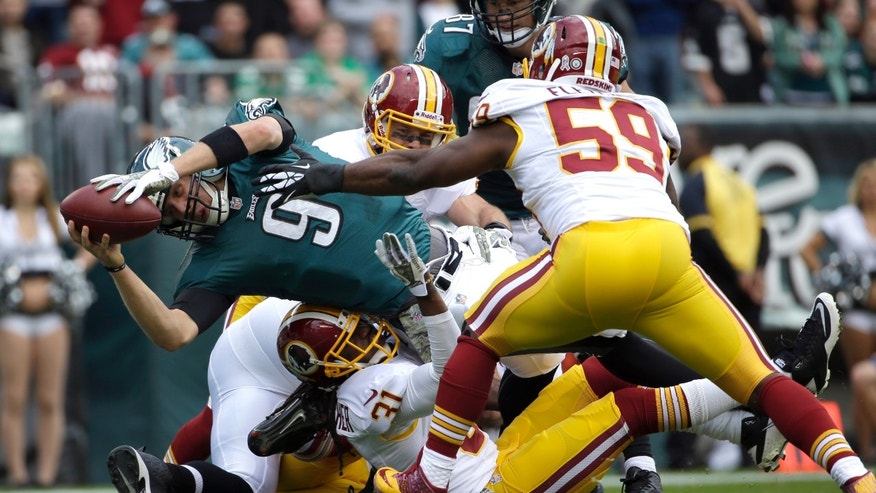 Philadelphia Eagles quarterback Nick Foles (9) dives into the end zone for a touchdown as Washington Redskins inside linebacker London Fletcher (59) reaches to stop him during the first half of an NFL football game in Philadelphia, Sunday, Nov. 17, 2013. (AP Photo/Matt Slocum)