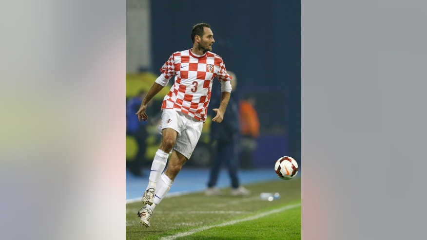 "In this Nov. 19, 2013 file picture Croatia's defender Josip Simunic, plays the ball during  a World Cup qualifying playoff second leg soccer match against Iceland, in Zagreb, Croatia. Croatia's World Cup qualification celebrations have been marred by apparent pro-Nazi chants by fans and defender Josip  Simunic. Croatia qualified for the World Cup with a 2-0 win over Iceland on Tuesday. Video footage shows Simunic taking a microphone to the field after the match and shouting to the fans: ""For the homeland!"" The fans respond: ""Ready!"" That was the war call used by the Croatian pro-Nazi puppet regime that ruled the state during World War II when tens of thousands Jews, Serbs and others perished in concentration camps. The Australian-born Simunic defended his action, saying ""some people have to learn some history."" (AP Photo/Darko Bandic)"