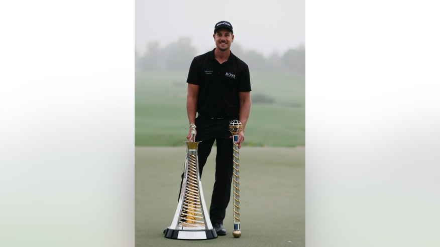 Henrik Stenson from Sweden poses for picture with the European tour race to Dubai and DP World Golf Championship trophies after the final round of DP World Golf Championship, in Dubai, United Arab Emirates, Sunday, Nov. 17, 2013. (AP Photo/Hassan Ammar)