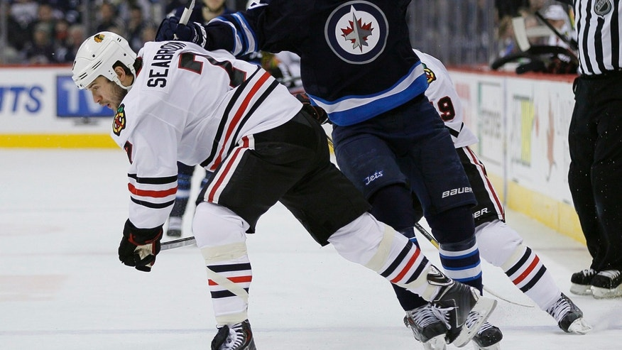 Winnipeg Jets' Evander Kane (9) and Chicago Blackhawks' Brent Seabrook (7) collide during the second period of an NHL hockey game in Winnipeg, Manitoba on Thursday, Nov. 21, 2013. (AP Photo/The Canadian Press, John Woods)