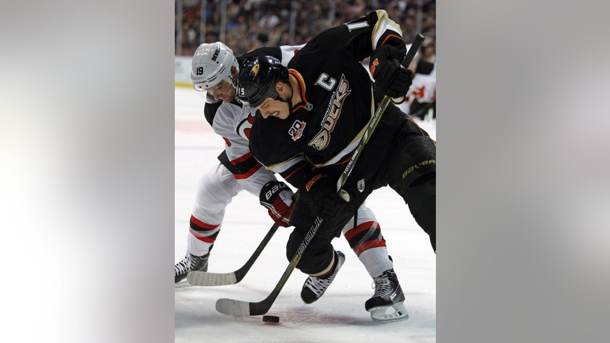 New Jersey Devils center Travis Zajac, left, battles for the puck with Anaheim Ducks center Ryan Getzlaf, right, in the first period of an NHL hockey game on Wednesday, Nov. 20, 2013 in Anaheim, Calif. (AP Photo/Alex Gallardo)