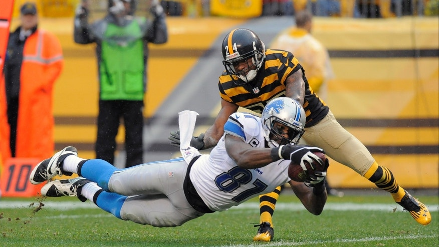 Detroit Lions wide receiver Calvin Johnson (81) dives for a touchdown after making a catch in front of Pittsburgh Steelers cornerback Ike Taylor (24) in the first half of an NFL football game on Sunday, Nov. 17, 2013, in Pittsburgh. (AP Photo/Don Wright)
