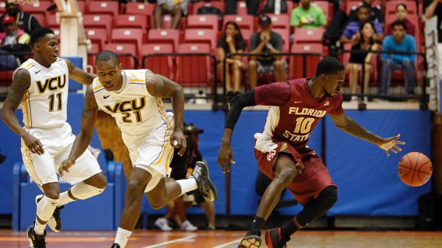 Florida State forward Okaro White, right, looses the ball while driving to the basket alongside VCU forward Treveon Graham, center, and VCU guard Rob Branderberg at an NCAA college basketball game in San Juan, Puerto Rico, Thursday, Nov. 21, 2013. (AP Photo/Ricardo Arduengo)