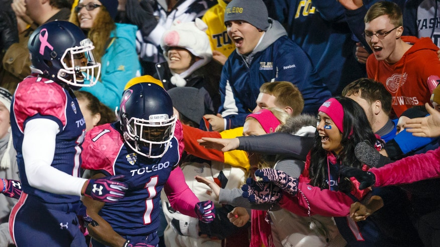 Toledo wide receiver Bernard Reedy (1) and wide receiver Dwight Macon, left, celebrate with fans after Reedy scored a touchdown against Northern Illinois in the third quarter of an NCAA college football game in Toledo, Ohio, Wednesday, Nov. 20, 2013. (AP Photo/Rick Osentoski)