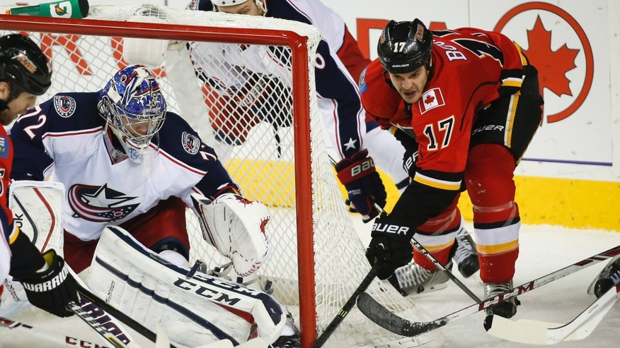 Columbus Blue Jackets goalie Sergei Bobrovsky, left, of Russia, blocks the net on Calgary Flames' Lance Bouma during the second period NHL hockey game in Calgary, Alberta, Wednesday, Nov. 20, 2013. (AP Photo/The Canadian Press, Jeff McIntosh)