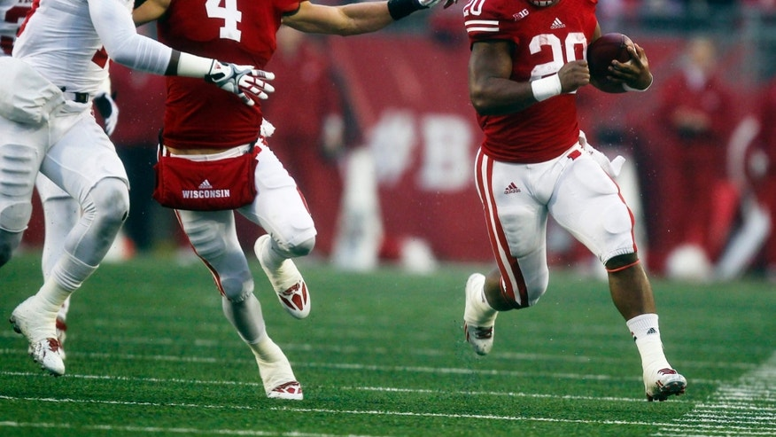 Wisconsin's Jared Abbrederis (4) blocks Indiana's Ryan Thompson (19) as James White (20) runs for a first down during first half of an NCAA college football game Saturday, Nov. 16, 2013, in Madison, Wis. White had 208 yards in Wisconsin's 51-3 win.  (AP Photo/Andy Manis)