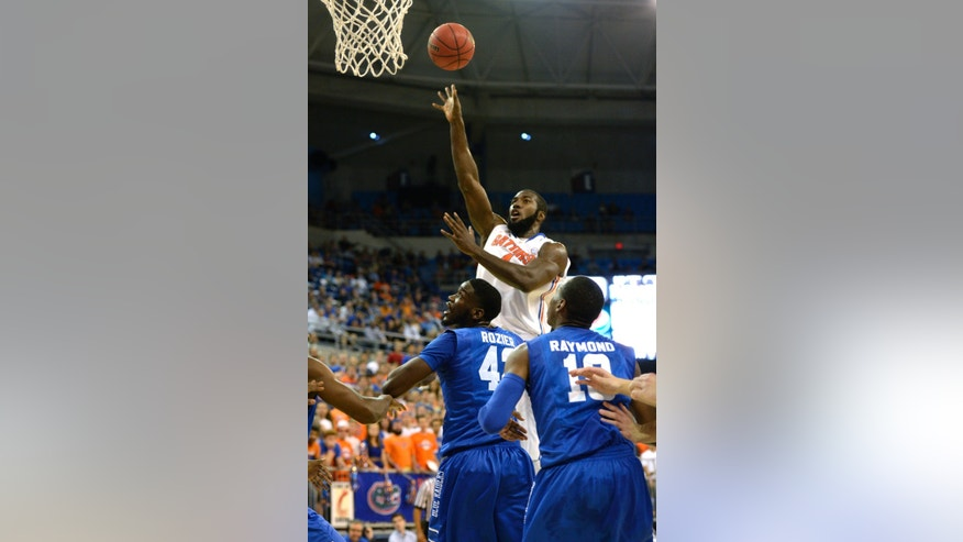 Florida center Patric Young (4) goes over the heads of Middle Tennessee forward Jacquez Rozier (42) and Middle Tennessee guard Jaqawn Raymond (10) for two points during an NCAA college baseketball game in Gainesville, Fla., Thursday, Nov. 21, 2013. (AP Photo/Phil Sandlin)