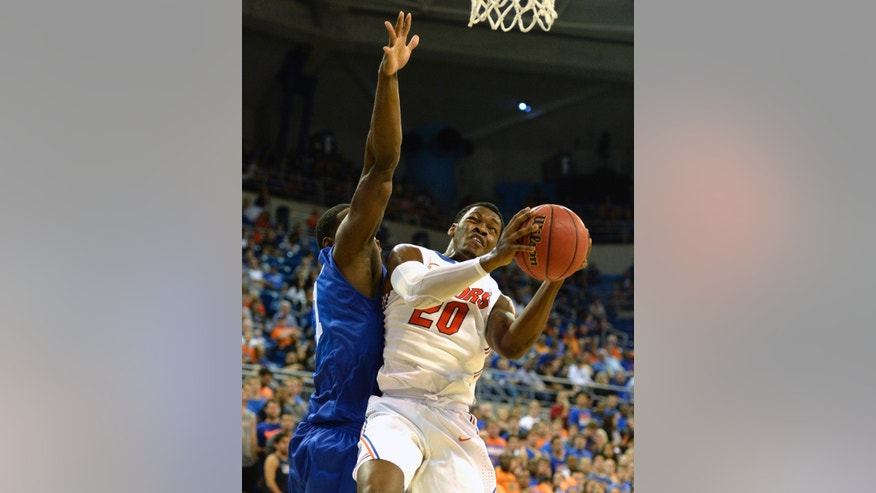 Florida guard Michael Frazier II (20) goes up against Middle Tennessee center Torin Walker (21) as he tries to get to the basket during an NCAA college baseketball game in Gainesville, Fla., Thursday, Nov. 21, 2013. (AP Photo/Phil Sandlin)