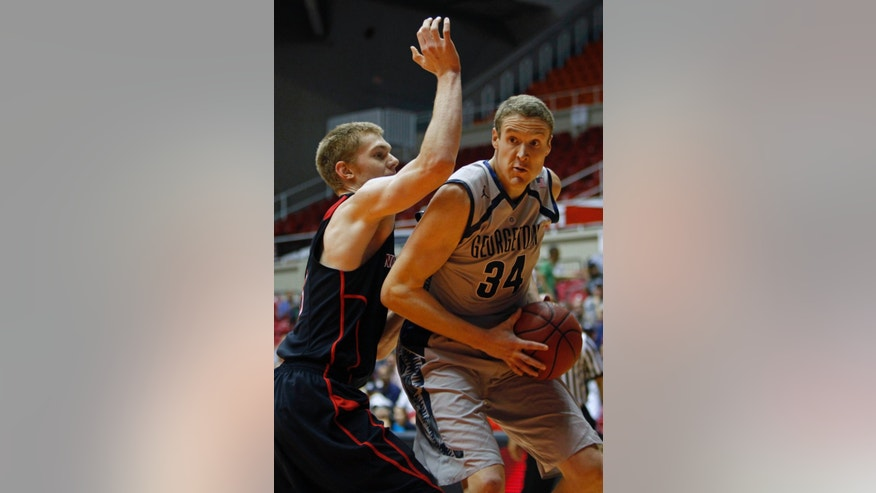 Northeastern forward Scott Eatherton, left, pressures Georgetown forward Nate Lubick during a NCAA college basketball game in San Juan, Puerto Rico, Thursday, Nov. 21, 2013. (AP Photo/Ricardo Arduengo)