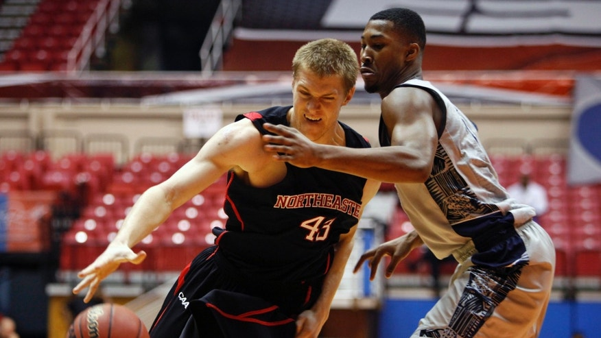 Northeastern forward Scott Eatherton, left, drives the ball against Georgetown's Mikael Hopkins during a NCAA college basketball game in San Juan, Puerto Rico, Thursday, Nov. 21, 2013. (AP Photo/Ricardo Arduengo)
