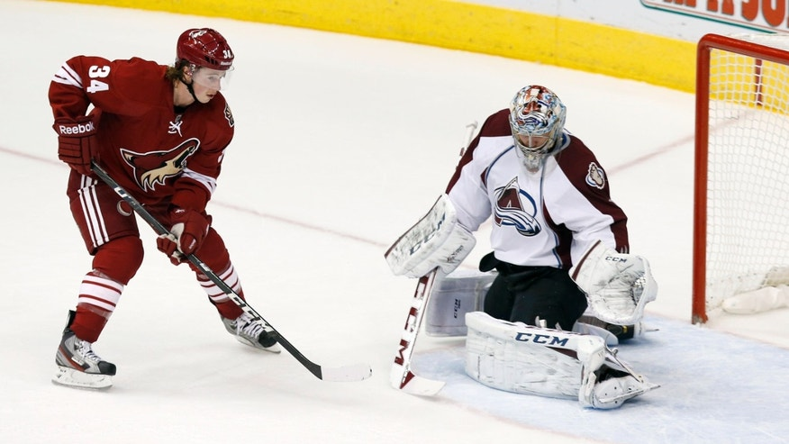 Colorado Avalanche's Semyon Varlamov, right, of Russia, makes a save on a shot by Phoenix Coyotes' Tim Kennedy (34) during the first period of an NHL hockey game Thursday, Nov. 21, 2013, in Glendale, Ariz. (AP Photo/Ross D. Franklin)