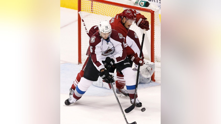 Colorado Avalanche's Cory Sarich, front, and Phoenix Coyotes' Shane Doan battle for the puck during the first period of an NHL hockey game Thursday, Nov. 21, 2013, in Glendale, Ariz. (AP Photo/Ross D. Franklin)