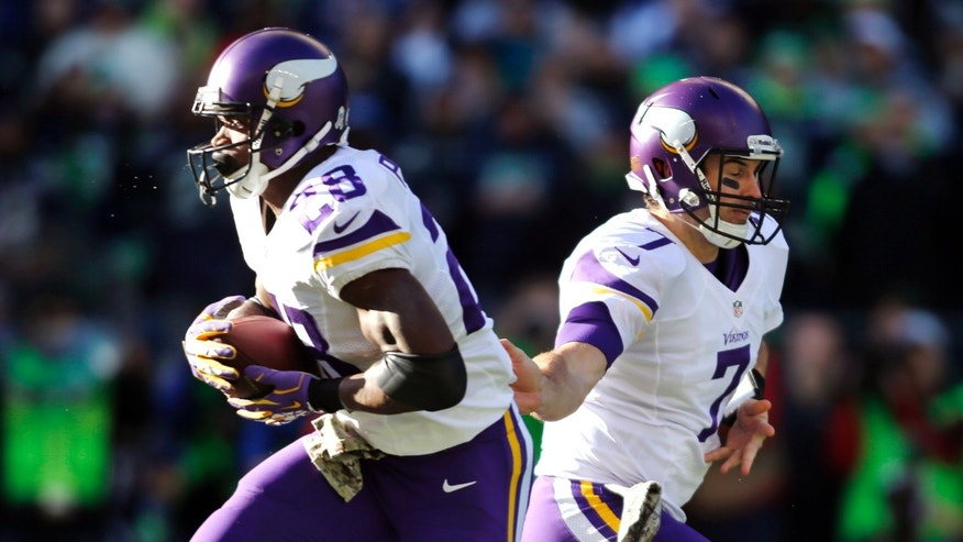Minnesota Vikings quarterback Christian Ponder (7) hands off to Adrian Peterson in the first half of an NFL football game Sunday, Nov. 17, 2013, in Seattle. (AP Photo/John Froschauer)