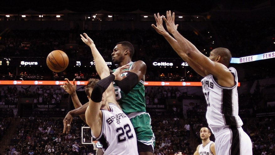 Boston Celtics' Jeff Green, center, is defended by San Antonio Spurs' Tiago Splitter (22), of Brazil, as he tries to score during the first half of an NBA basketball game, Wednesday,  Nov. 20, 2013, in San Antonio. (AP Photo/Eric Gay)