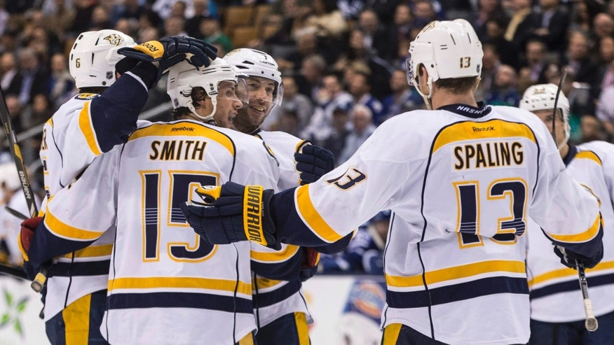 Nashville Predators' Craig Smith (15) celebrates with teammates after scoring his team's fourth goal against Toronto Maple Leafs during the third period of an NHL hockey game, Thursday, Nov. 21, 2013 in Toronto. (AP Photo/The Canadian Press, Chris Young)