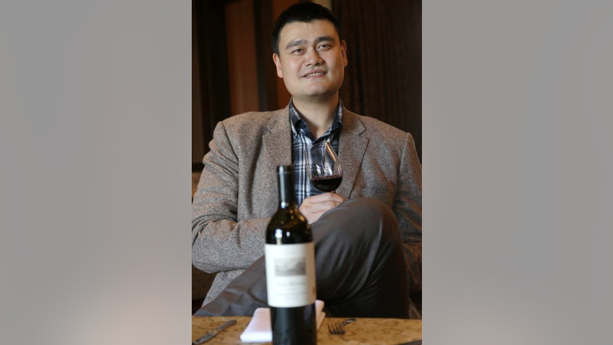 ADVANCE FOR WEEKEND EDITIONS, NOV. 23-24 - FILE - In this Nov. 15, 2013 file photo, former Houston Rockets basketball player Yao Ming sips a glass of his new signature Cabernet Sauvignon red wine at a Houston restaurant. Yao wears a lot of different hats since hanging up his size 18 shoes and retiring in 2011.  (AP Photo/Pat Sullivan, File)