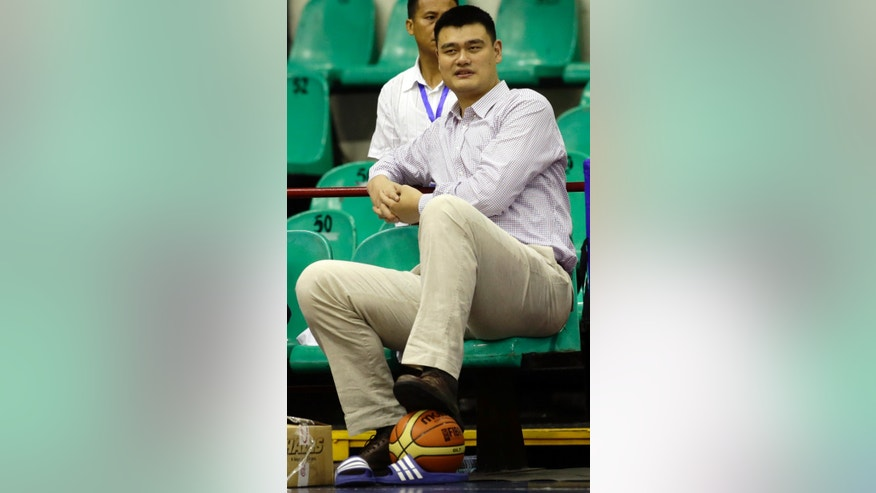ADVANCE FOR WEEKEND EDITIONS, NOV. 23-24 - FILE - In this May 5, 2013 file photo, former NBA Houston Rockets basketball player Yao Ming watches his Shanghai Sharks team practice at a sports complex at suburban Pasig city east of Manila, Philippines. Yao wears a lot of different hats since hanging up his size 18 shoes and retiring in 2011. (AP Photo/Bullit Marquez, File)