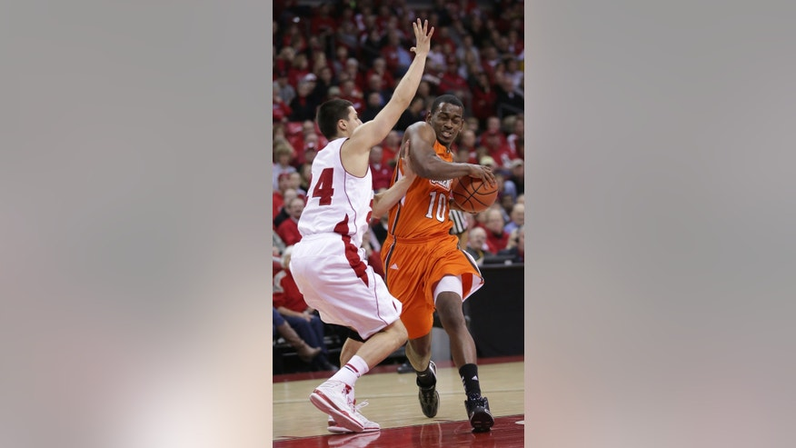 Bowling Green's Craig Sealey (10) tries to drive past Wisconsin's Bronson Koenig (24) during the first half of an NCAA college basketball game on Thursday, Nov. 21, 2013, in Madison, Wis. (AP Photo/Craig Schreiner)