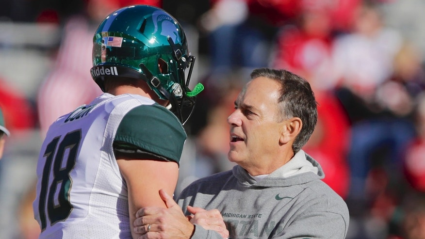 Michigan State head coach Mark Dantonio, right, talks to quarterback Connor Cook (18) during warm ups before an NCAA college football game against Nebraska  in Lincoln, Neb., Saturday, Nov. 16, 2013. (AP Photo/Nati Harnik)