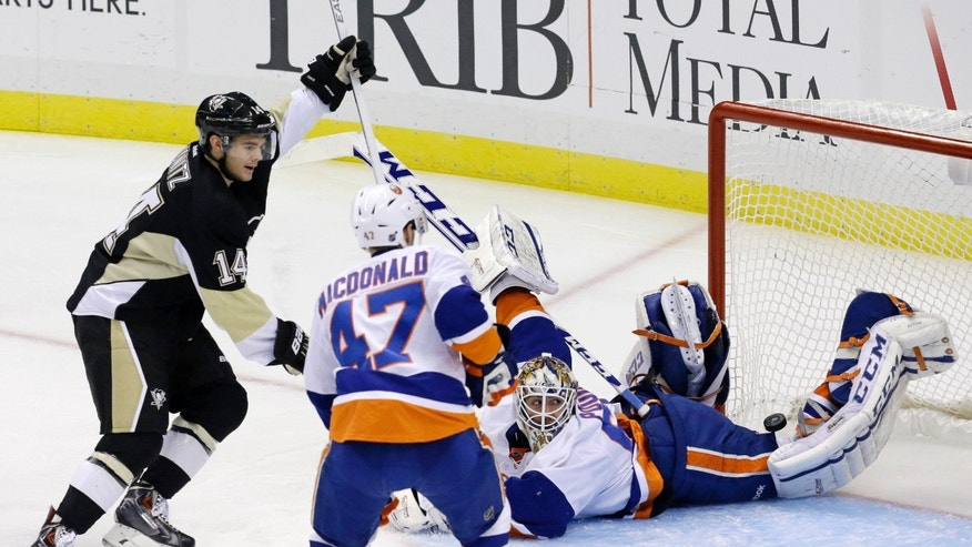 Pittsburgh Penguins' Chris Kunitz (14) begins to celebrate his first-period goal as New York Islanders goalie Kevin Poulin (60) looks back to see the puck bounce out of the net during an NHL hockey game in Pittsburgh, Friday, Nov. 22, 2013. (AP Photo/Gene J. Puskar)