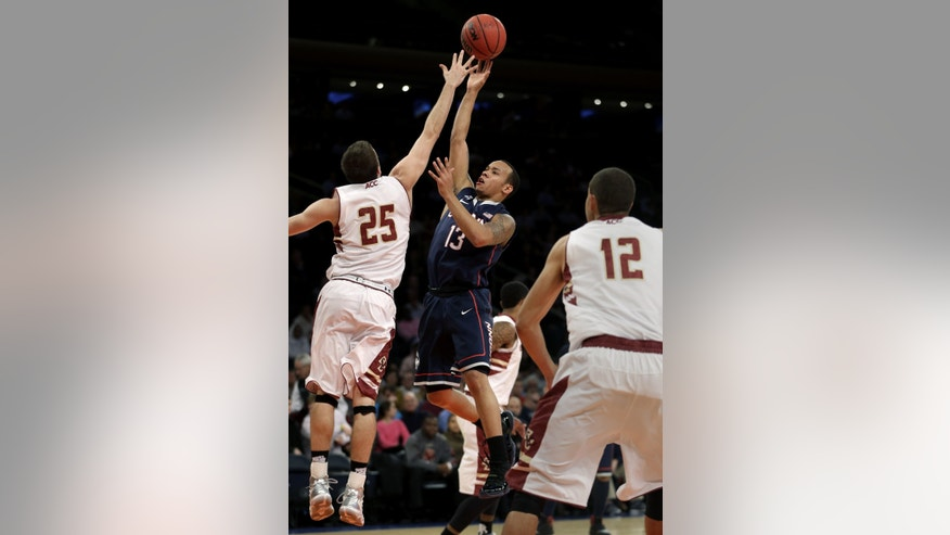Connecticut's Shabazz Napier, center, shoots over Boston College's Joe Rahon, left, during the first half of an NCAA college basketball game on Thursday, Nov. 21, 2013, in New York. (AP Photo/Seth Wenig)