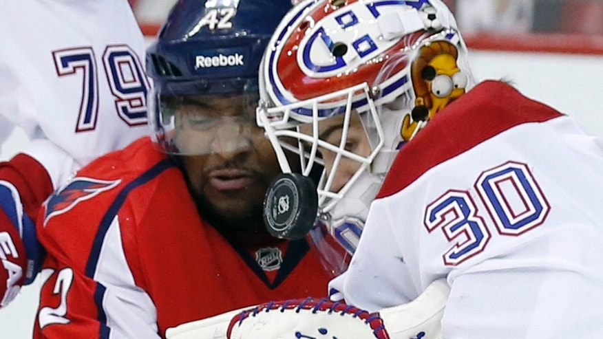 Washington Capitals right wing Joel Ward, left, and Montreal Canadiens goalie Peter Budaj (30), of Czech Republic, stand by as the puck bounces off Budaj's shoulder, in the first period of an NHL hockey game Friday, Nov. 22, 2013, in Washington. (AP Photo/Alex Brandon)