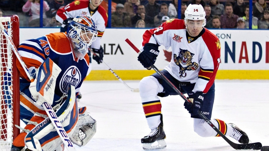 Florida Panthers Tomas Fleischmann (14) looks for the rebound as Edmonton Oilers goalie Devan Dubnyk (40) makes the save during first period NHL hockey action in Edmonton, Alberta, on Thursday Nov. 21, 2013. (AP Photo/The Canadian Press, Jason Franson)