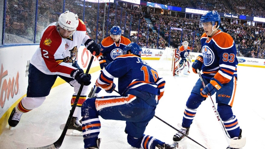 Florida Panthers' Jimmy Hayes (12) battles in the corner with Edmonton Oilers' Justin Schultz (19), Anton Belov (77) and Ryan Nugent-Hopkins (93) during first period NHL hockey action in Edmonton, Alberta, on Thursday Nov. 21, 2013. (AP Photo/The Canadian Press, Jason Franson)