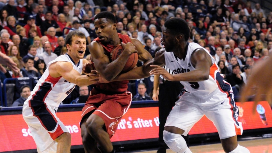 Gonzaga's Kevin Pangos, left,  and Gary Bell Jr., right,  defend Washington State's Ike Iroegbu in the first half of an NCAA college basketball game, Thursday, Nov. 21, 2013, in Spokane, Wash. (AP Photo/Jed Conklin)