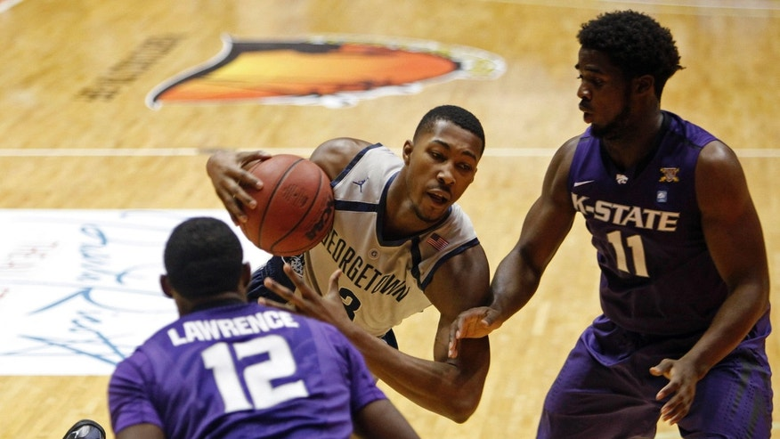 Kansas State forward Nino Williams, right, and teammate Omari Lawrence pressure Georgetown forward Mikael Hopkins during an NCAA college basketball game in San Juan, Puerto Rico, Friday, Nov. 22, 2013. (AP Photo/Ricardo Arduengo)