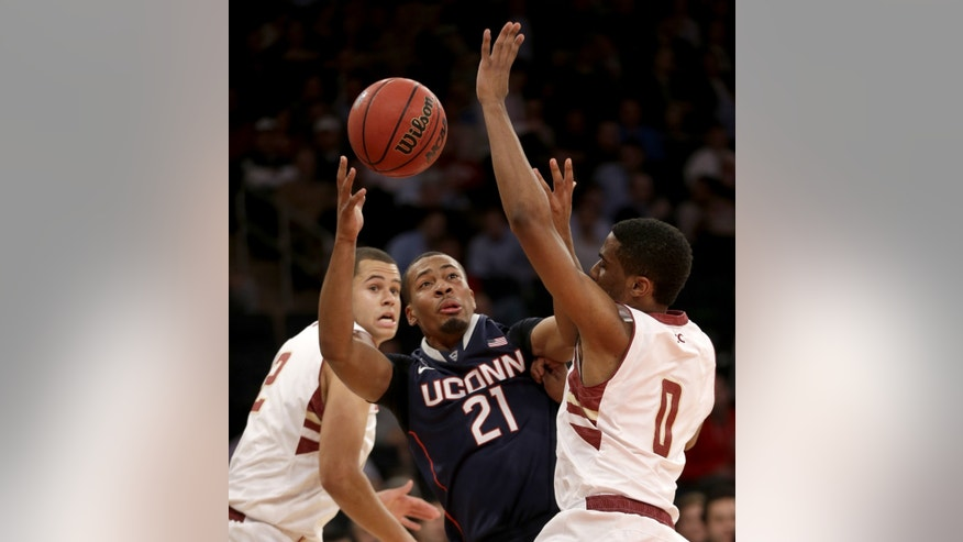 Connecticut's Omar Calhoun, center, fights for control of the ball with Boston College's Garland Owens, right, and Ryan Anderson during the first half of an NCAA college basketball game on Thursday, Nov. 21, 2013, in New York. (AP Photo/Seth Wenig)