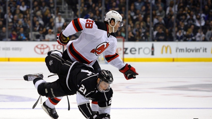 Los Angeles Kings right wing Matt Frattin, below, is tripped by New Jersey Devils right wing Jaromir Jagr, of the Czech Republic, during the second period of an NHL hockey game, Thursday, Nov. 21, 2013, in Los Angeles. (AP Photo/Mark J. Terrill)