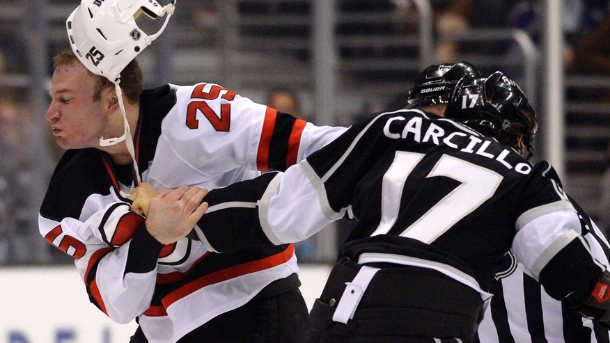 New Jersey Devils right wing Cam Janssen, left, and Los Angeles Kings left wing Daniel Carcillo fight during the first period of an NHL hockey game on Thursday, Nov. 21, 2013, in Los Angeles. (AP Photo/Mark J. Terrill)