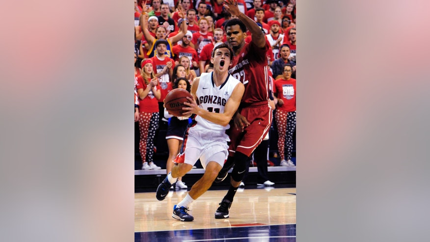 Gonzaga's David Stockton (11) drives against Washington State's Royce Woolridge (22) in the first half of an NCAA college basketball game, Thursday, Nov. 21, 2013, in Spokane, Wash. (AP Photo/Jed Conklin)