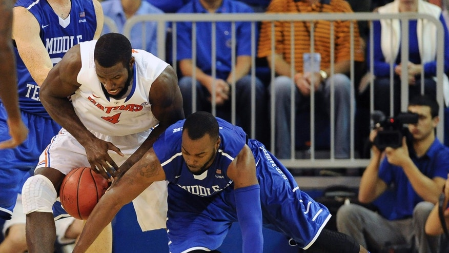 Florida center Patric Young (4) tries to get the ball after Middle Tennessee forward Neiko Hunter (1) looses the ball in the second half of an NCAA college basketball game in Gainesville, Fla., Thursday, Nov. 21, 2013. Florida defeated Middle Tennessee 79-59.  (AP Photo/Phil Sandlin)