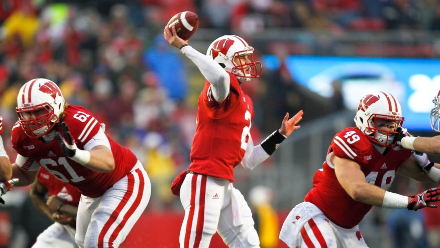 Wisconsin quarterback Joel Stave, center, passes with protection from teammates Tyler Marz, left, and Sam Arneson during the second half of an NCAA college football game against Indiana Saturday, Nov. 16, 2013, in Madison, Wis.  (AP Photo/Andy Manis)