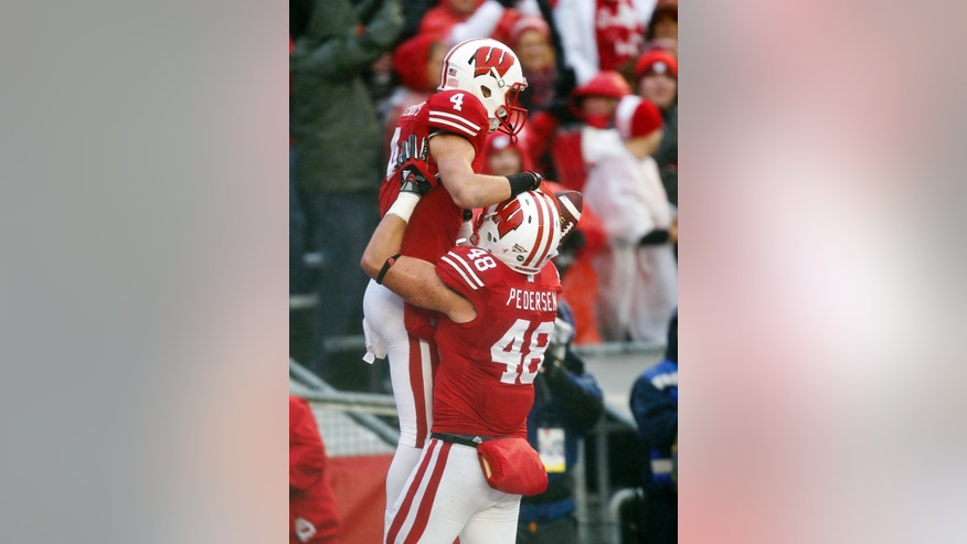 Wisconsin's Jacob Pedersen (48) lifts Jared Abbrederis after Abbrederis' touchdown during the first half of an NCAA college football game against Indiana Saturday, Nov. 16, 2013, in Madison, Wis. (AP Photo/Andy Manis)
