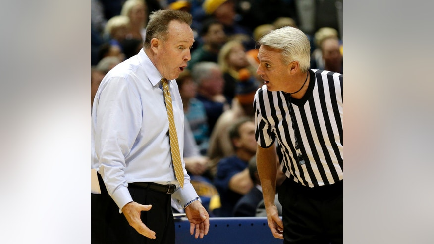 New Hampshires head coach Bill Herrion, left, argues a call with a referee during the first half of an NCAA college basketball game against Marquette, Thursday, Nov. 21, 2013, in Milwaukee. (AP Photo/Jeffrey Phelps)