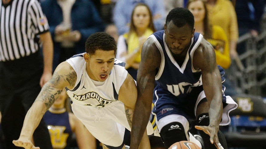 Marquette's Juan Anderson, left, and New Hampshire's Patrick Konan reach for a loose ball during the first half of an NCAA college basketball game Thursday, Nov. 21, 2013, in Milwaukee. (AP Photo/Jeffrey Phelps)