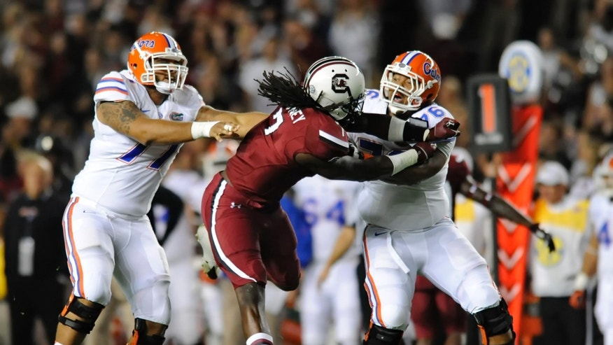 South Carolina's Jadeveon Clowney (7) tangles with Florida's Max Garcia, right, and Ian Silberman during the first half of an NCAA college football game Saturday, Nov. 16, 2013, at Williams-Brice Stadium in Columbia, S.C. South Carolina won 19-14. (AP Photo/ Richard Shiro)