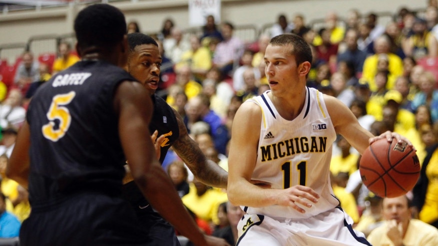 Long Beach State's Mike Caffey, left, and Kris Gulley pressure Michigan's Nik Stauskas during an NCAA college basketball game in San Juan, Puerto Rico, Thursday, Nov. 21, 2013. (AP Photo/Ricardo Arduengo)