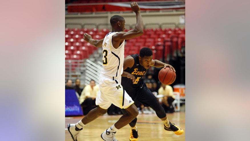 Michigan's Carl LeVert, left, pressures Long Beach State's Mike Caffey during an NCAA college basketball game in San Juan, Puerto Rico, Thursday, Nov. 21, 2013. (AP Photo/Ricardo Arduengo)