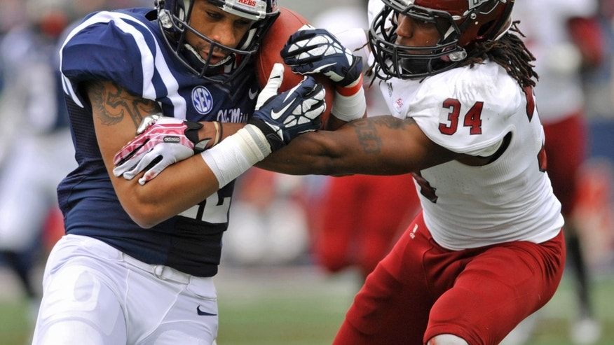 Mississippi receiver Donte Moncrief (12) holds onto the ball after a catch with Troy cornerback Ethan Davis (34) during the second quarter of an NCAA college football game on Saturday, Nov. 16, 2013, in Oxford, Miss. Mississippi won 51-21. (AP Photo/ The Daily Mississippian, Austin McAfee)