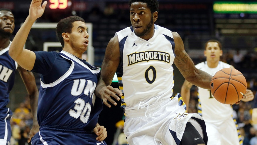 Marquette's Jamil Wilson (0) drives against New Hampshires' Daniel Dion (30) during the first half of an NCAA college basketball game Thursday, Nov. 21, 2013, in Milwaukee. (AP Photo/Jeffrey Phelps)